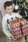 Το αγόρι είναι έκπληκτο με ένα μεγάλο δώρο Χριστουγέννων Στοκ εικόνα με δικαίωμα ελεύθερης χρήσης