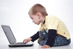 Το αγόρι είναι έντονο στο lap-top στοκ εικόνες
