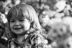 Το αγόρι είναι ευτυχές με τη θαυμάσια ηλιόλουστη ημέρα Χαμογελώντας αγόρι στην άνθιση Στοκ εικόνες με δικαίωμα ελεύθερης χρήσης