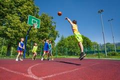 Το αγόρι εκτελεί τον αποκρουστικό πυροβολισμό στο παιχνίδι καλαθοσφαίρισης Στοκ Φωτογραφία