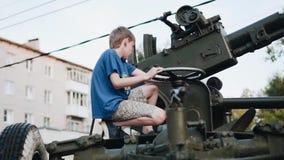 Το αγόρι ελέγχει το αντιαεροπορικό πυροβόλο όπλο που στέκεται κοντά στο μουσείο απόθεμα βίντεο