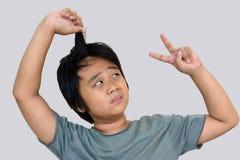 Το αγόρι εξετάζει μακρυμάλλη με το γκρίζο υπόβαθρο Στοκ φωτογραφία με δικαίωμα ελεύθερης χρήσης