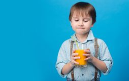 Το αγόρι εξετάζει το χυμό από πορτοκάλι στοκ φωτογραφίες