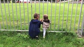 Το αγόρι εξηγεί τους κανόνες στο κορίτσι στον αγώνα ποδοσφαίρου από το φράκτη απόθεμα βίντεο