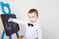 Το αγόρι επισύρει την προσοχή μια κιμωλία σε ένα χαρτόνι Στοκ Φωτογραφίες