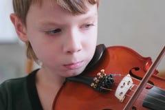 Το αγόρι 8 ετών παίζει το βιολί χρησιμοποιώντας τις σημειώσεις Πρόσωπο cloe-επάνω στοκ φωτογραφία με δικαίωμα ελεύθερης χρήσης
