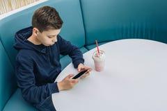Το αγόρι εφήβων κάθεται στον πίνακα στον καφέ, πίνει milkshake, χρησιμοποιεί το smartphone Το αγόρι παίζει τα παιχνίδια στο smart Στοκ φωτογραφία με δικαίωμα ελεύθερης χρήσης