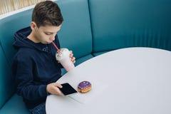 Το αγόρι εφήβων κάθεται στον πίνακα στον καφέ, πίνει milkshake, χρησιμοποιεί το smartphone Το αγόρι παίζει τα παιχνίδια στο smart Στοκ Φωτογραφίες