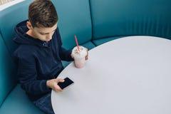 Το αγόρι εφήβων κάθεται στον πίνακα στον καφέ, πίνει milkshake, χρησιμοποιεί το smartphone Το αγόρι παίζει τα παιχνίδια στο smart Στοκ Φωτογραφία