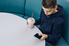 Το αγόρι εφήβων κάθεται στον πίνακα στον καφέ, πίνει milkshake, χρησιμοποιεί το smartphone Το αγόρι παίζει τα παιχνίδια στο smart Στοκ εικόνα με δικαίωμα ελεύθερης χρήσης