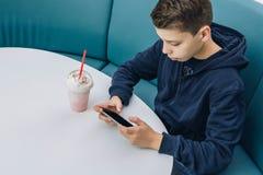 Το αγόρι εφήβων κάθεται στον πίνακα στον καφέ, πίνει milkshake, χρησιμοποιεί το smartphone Το αγόρι παίζει τα παιχνίδια στο smart Στοκ Εικόνα