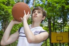Το αγόρι εφήβων με μια σφαίρα για την καλαθοσφαίριση παίζει την καλαθοσφαίριση Στοκ φωτογραφία με δικαίωμα ελεύθερης χρήσης
