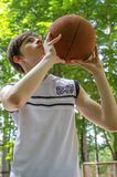 Το αγόρι εφήβων με μια σφαίρα για την καλαθοσφαίριση παίζει την καλαθοσφαίριση Στοκ Εικόνα