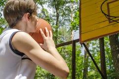 Το αγόρι εφήβων με μια σφαίρα για την καλαθοσφαίριση παίζει την καλαθοσφαίριση Στοκ Φωτογραφία