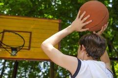 Το αγόρι εφήβων με μια σφαίρα για την καλαθοσφαίριση παίζει την καλαθοσφαίριση Στοκ Φωτογραφίες
