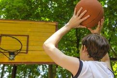 Το αγόρι εφήβων με μια σφαίρα για την καλαθοσφαίριση παίζει την καλαθοσφαίριση Στοκ Εικόνες