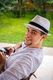 Το αγόρι εφήβων με το άσπρο καπέλο χαλαρώνει στον κήπο Στοκ Εικόνες