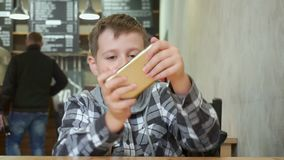 Το αγόρι εφήβων παίζει ενεργά το παιχνίδι στο smartphone Κάθεται σε έναν καφέ απόθεμα βίντεο