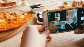 Το αγόρι εφήβων παίρνει μια φωτογραφία των τροφίμων σε ένα smartphone Ιαπωνικοί ρόλοι σουσιών και ιταλική πίτσα στον πίνακα εστια απόθεμα βίντεο