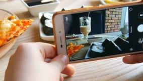 Το αγόρι εφήβων παίρνει μια φωτογραφία των τροφίμων σε ένα smartphone Ιταλική πίτσα στον πίνακα εστιατορίων απόθεμα βίντεο