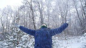 Το αγόρι εφήβων ρίχνει το χιόνι στο χειμερινό δασικό ενεργό τρόπο ζωής, χειμερινή δραστηριότητα, υπαίθρια έννοια χειμερινών αγώνω φιλμ μικρού μήκους