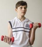 Το αγόρι εφήβων σε ένα άσπρο πουκάμισο χωρίς μανίκια κάνει τις ασκήσεις με τους αλτήρες στοκ εικόνες