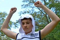 Το αγόρι εφήβων σε ένα άσπρο πουκάμισο χωρίς μανίκια με τα χέρια σε μια χειρονομία της νίκης στοκ εικόνες με δικαίωμα ελεύθερης χρήσης