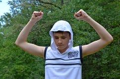 Το αγόρι εφήβων σε ένα άσπρο πουκάμισο χωρίς μανίκια με τα χέρια σε μια χειρονομία της νίκης στοκ εικόνα
