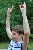 Το αγόρι εφήβων σε ένα άσπρο πουκάμισο χωρίς μανίκια με τα χέρια σε μια χειρονομία της νίκης στοκ εικόνες