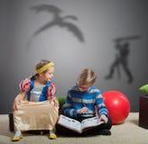 Το αγόρι διαβάζει ένα βιβλίο στη μικρή αδελφή του Στοκ φωτογραφία με δικαίωμα ελεύθερης χρήσης