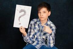Το αγόρι κάθεται, ένα καθαρό φύλλο, στο στούντιο Στοκ Εικόνα