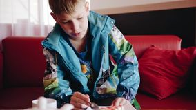 Το αγόρι κάθεται σε έναν καφέ και τρώει ένα κέικ και μιλά στον πατέρα του Εξετάστε το αγόρι o απόθεμα βίντεο