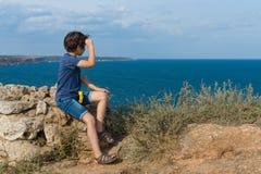 Το αγόρι κάθεται στην υψηλή ακτή Στοκ Εικόνες