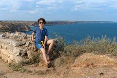 Το αγόρι κάθεται στην υψηλή ακτή Στοκ Φωτογραφία