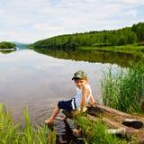 Το αγόρι κάθεται στις όχθεις του ποταμού. Στοκ Εικόνα