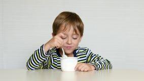 Το αγόρι κάθεται στον πίνακα και τρώει το γιαούρτι από ένα βάζο, δοκιμάζοντας τις συγκινήσεις: ευτυχία, χαρά, ευχαρίστηση Τρόφιμα απόθεμα βίντεο