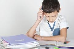 Το αγόρι κάθεται στο γραφείο που κάνει την εργασία του στοκ φωτογραφία