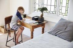 Το αγόρι κάθεται στο γραφείο στην κρεβατοκάμαρα με την ψηφιακή ταμπλέτα που κάνει την εργασία Στοκ φωτογραφίες με δικαίωμα ελεύθερης χρήσης
