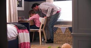 Το αγόρι κάθεται στο γραφείο στην κρεβατοκάμαρα που κάνει την εργασία που ενισχύεται από τον πατέρα απόθεμα βίντεο
