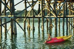 Το αγόρι κάθεται στο καγιάκ με το ξύλινο υπόβαθρο γεφυρών Στοκ Εικόνες