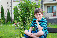 Το αγόρι κάθεται στο banch στοκ φωτογραφίες