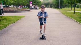 Το αγόρι κάνει πατινάζ σε ένα μηχανικό δίκυκλο σε ένα πάρκο με τους ανθρώπους στο θερινό ηλιόλουστο καιρό που έχει μια καλή διάθε απόθεμα βίντεο