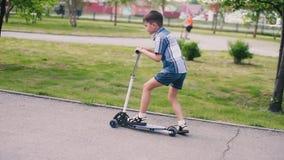 Το αγόρι κάνει πατινάζ σε ένα μηχανικό δίκυκλο στο πάρκο στο θερινό ηλιόλουστο καιρό που έχει μια καλή διάθεση HD απόθεμα βίντεο