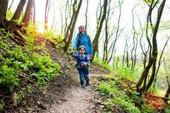 Το αγόρι και η μητέρα του περπατούν μέσω των ξύλων στοκ φωτογραφία με δικαίωμα ελεύθερης χρήσης