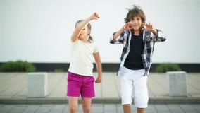 Το αγόρι και το κορίτσι έχουν τη διασκέδαση από κοινού Έχουν μια μάχη χορού που στέκεται στις πέτρες απόθεμα βίντεο