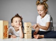 Το αγόρι και το κορίτσι δύο παιδιών στις άσπρες μπλούζες είναι στο πάτωμα και παίζουν Jenga στοκ εικόνα