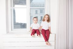 Το αγόρι και το κορίτσι είναι αδελφός και η αδελφή κάθεται στο windowsill στο παράθυρο στοκ φωτογραφίες με δικαίωμα ελεύθερης χρήσης