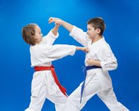 Το αγόρι και το κορίτσι είναι εκπαιδευμένοι karate διατρήσεις και φραγμοί Στοκ Φωτογραφίες