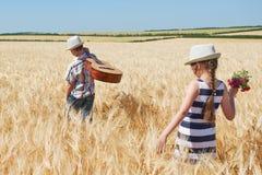 Το αγόρι και το κορίτσι παιδιών με την κιθάρα είναι στον κίτρινο τομέα σίτου, φωτεινός ήλιος, θερινό τοπίο Στοκ Φωτογραφίες