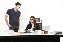 Το αγόρι και το κορίτσι συζητούν την εργασία στο σημειωματάριο στοκ εικόνες